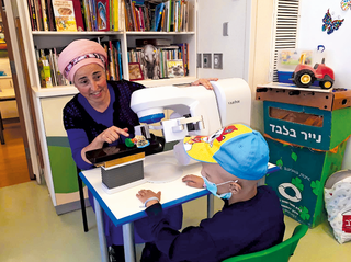 """שטינמנץ, הדגם ואחד הילדים המטופלים. """"לומדים להכיר את הסביבה"""".צילום: דוברות הדסה"""